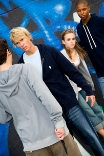 Confrontation between two young men and a group of friends in front of a graffiti covered wallの写真素材 [FYI02120502]
