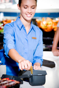 Portrait of a supermarket checkout assistant using a credit card machineの写真素材 [FYI02120512]