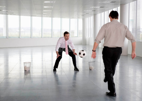 Two businessman playing football in an empty officeの写真素材 [FYI02120517]