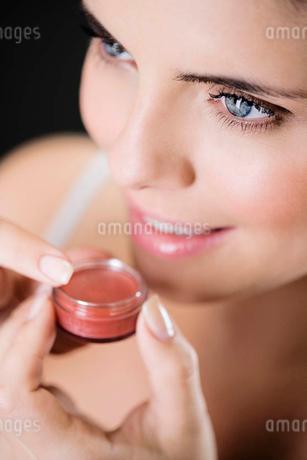 Woman applying lip glossの写真素材 [FYI02120538]