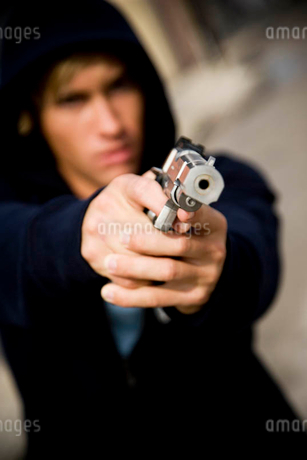 Portrait of a young man holding a gunの写真素材 [FYI02120571]