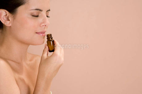 Woman smelling a bottle of essential oilの写真素材 [FYI02120581]