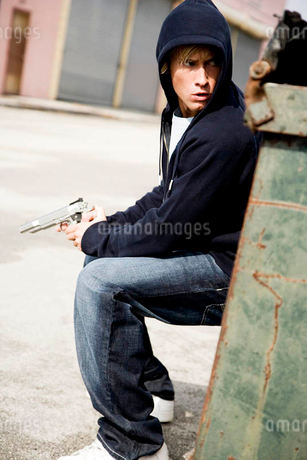 Portrait of a young man holding a gun sheltering behind a binの写真素材 [FYI02120609]