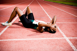 Female athlete resting on a running trackの写真素材 [FYI02120611]