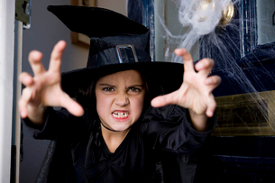 Young  girl at the front door, dressed up as a witch for Halloweenの写真素材 [FYI02120616]