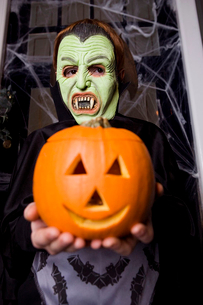Child in a Count Dracula costume at Hallowe'en, holding a pumpkin with a carved faceの写真素材 [FYI02120632]