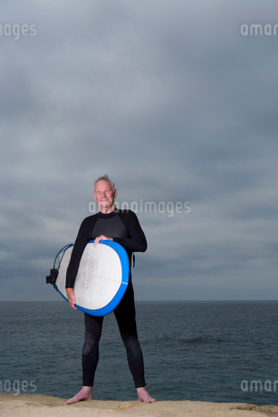 Male surfer in wetsuit with surfboard by beach, portraitの写真素材 [FYI02120649]