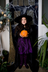 Girl in a witch's costume at a Hallowe'en party, holding a pumpkinの写真素材 [FYI02120674]