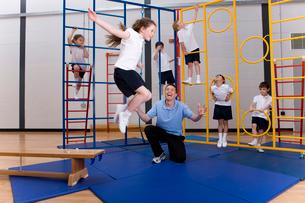 Gym teacher watching school girl jumping off climbing equipmentの写真素材 [FYI02120677]