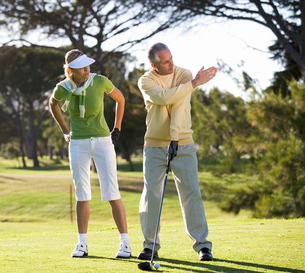 Man teaching a woman how to play golfの写真素材 [FYI02120681]