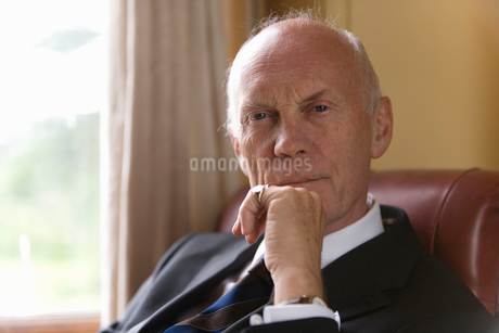Senior businessman in armchair with hand to face, portrait, close-upの写真素材 [FYI02120720]