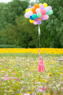 Girl holding bunch of balloons among wildflowers in sunny meadowの写真素材 [FYI02120725]