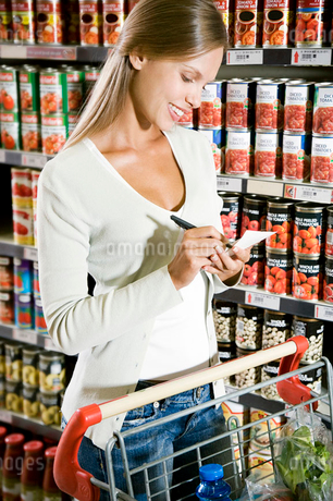 Woman ticking off her shopping listの写真素材 [FYI02120726]