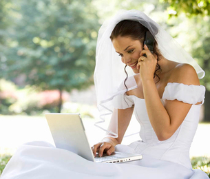 A bride using a laptop and mobile phoneの写真素材 [FYI02120735]
