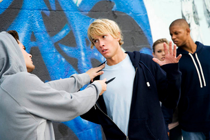 Confrontation between two young men and a group of friends in front of a graffiti covered wallの写真素材 [FYI02120743]