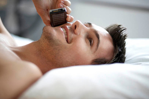 Young man laying on a bed talking on a mobile phone, close-upの写真素材 [FYI02120765]