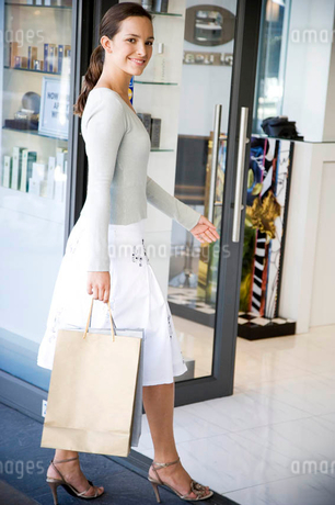Woman on a shopping trip walking into a storeの写真素材 [FYI02120768]