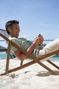 A mature man sitting in a deck chair on a cell phoneの写真素材 [FYI02120789]