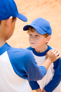 older boy talking down to younger boy at baseball practiceの写真素材 [FYI02120823]