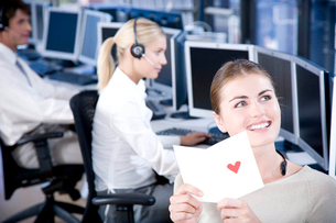 Woman in a call centre smiling as she opens a Valentines card.の写真素材 [FYI02120837]