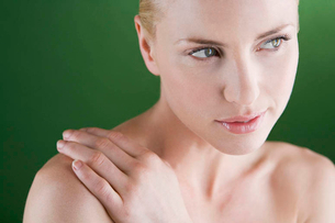 A portrait of a young blonde woman with her hand on her shoulderの写真素材 [FYI02120852]