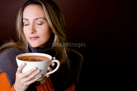 A mid adult woman holding a cup of soupの写真素材 [FYI02120860]