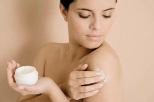 Woman applying moisturising creamの写真素材 [FYI02120863]