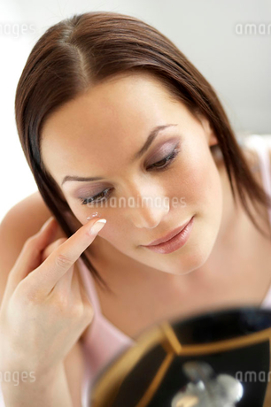 Young woman inserting a contact lensの写真素材 [FYI02120881]