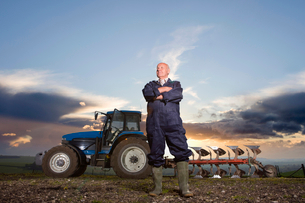 Farmer standing with arms crossed in field with tractor and plough in backgroundの写真素材 [FYI02120889]