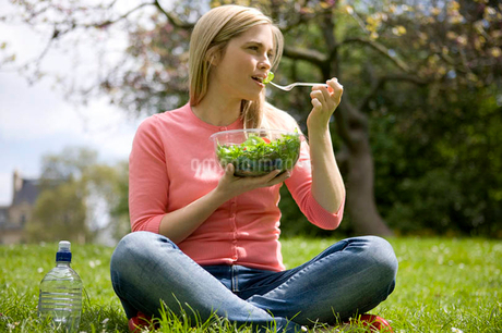 A young woman eating a bowl of salad in a parkの写真素材 [FYI02120907]