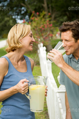 couple in garden with jug of lemonadeの写真素材 [FYI02120912]