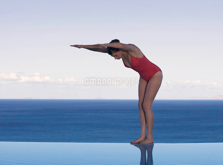 A woman preparing to dive into a poolの写真素材 [FYI02120914]