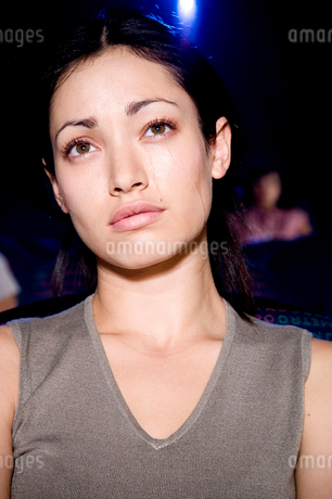 Woman watching a sad film at the cinemaの写真素材 [FYI02120928]
