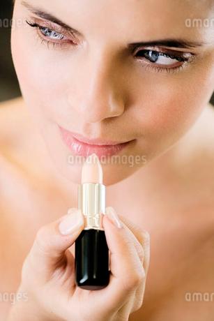 Woman applying lip gloss or top coatの写真素材 [FYI02120936]