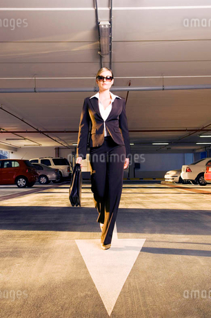 A businesswoman walking in a car parkの写真素材 [FYI02120942]