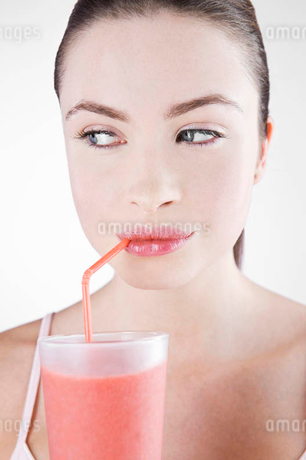 A Young Woman Drinking A Fruit Drink Through A Strawの写真素材 [FYI02120946]