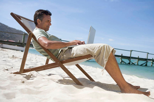 A mature man sitting in a deck chair using a laptopの写真素材 [FYI02120960]