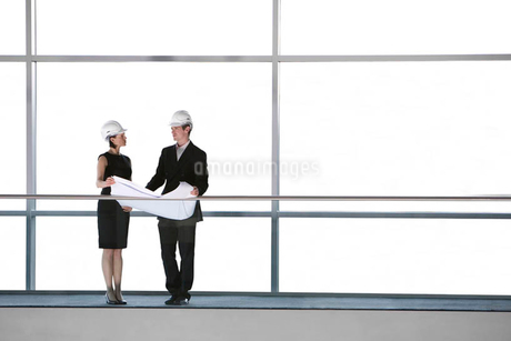 Two architects or developers standing on a walkway of an office building, looking at plansの写真素材 [FYI02120967]