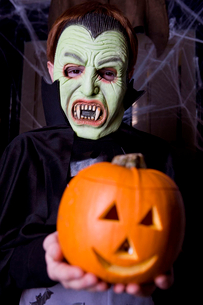 Child in a Count Dracula costume at Hallowe'en, holding a pumpkin with a carved faceの写真素材 [FYI02120978]