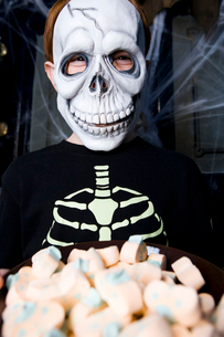 Boy in a skeleton costume at a Hallowe'en party, holding a tray of sweetsの写真素材 [FYI02120989]