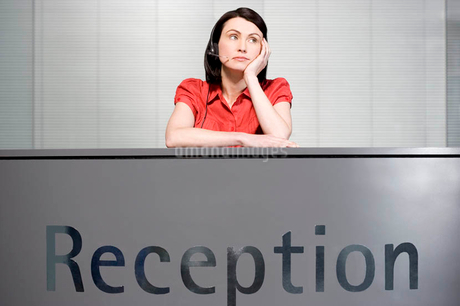 Office receptionist in a red blouse, looking boredの写真素材 [FYI02121007]