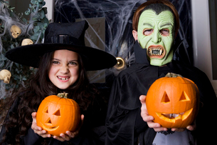 Children in Hallowe'en costumes, holding pumpkins with carved facesの写真素材 [FYI02121009]