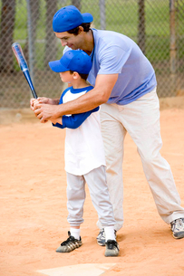 Young boy being taught how to swing a baseball batの写真素材 [FYI02121014]