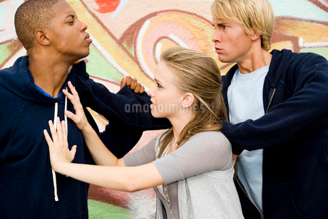 Two men fighting over a girl in front of a graffiti covered wallの写真素材 [FYI02121021]