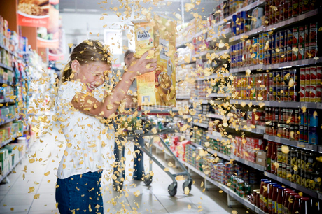 Naughty young girl emptying cereal packet in a supermarketの写真素材 [FYI02121040]