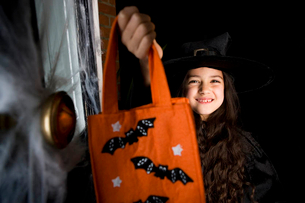 Girl in costume at a Hallowe'en party, holding an orange party bagの写真素材 [FYI02121053]