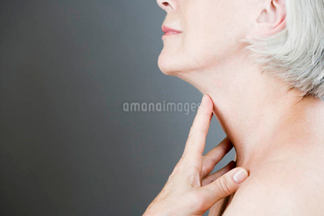A senior woman touching her neckの写真素材 [FYI02121074]