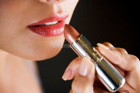 Woman applying red lipstick, close-up of mouthの写真素材 [FYI02121079]