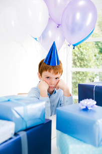 boy sulking at birthday partyの写真素材 [FYI02121081]