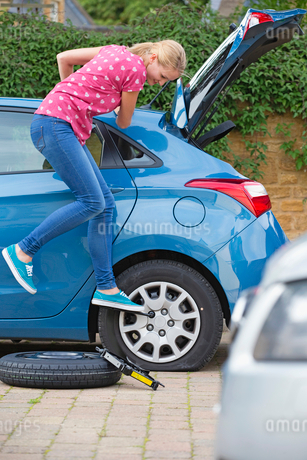Woman Changing Flat Tyre On Carの写真素材 [FYI02121107]